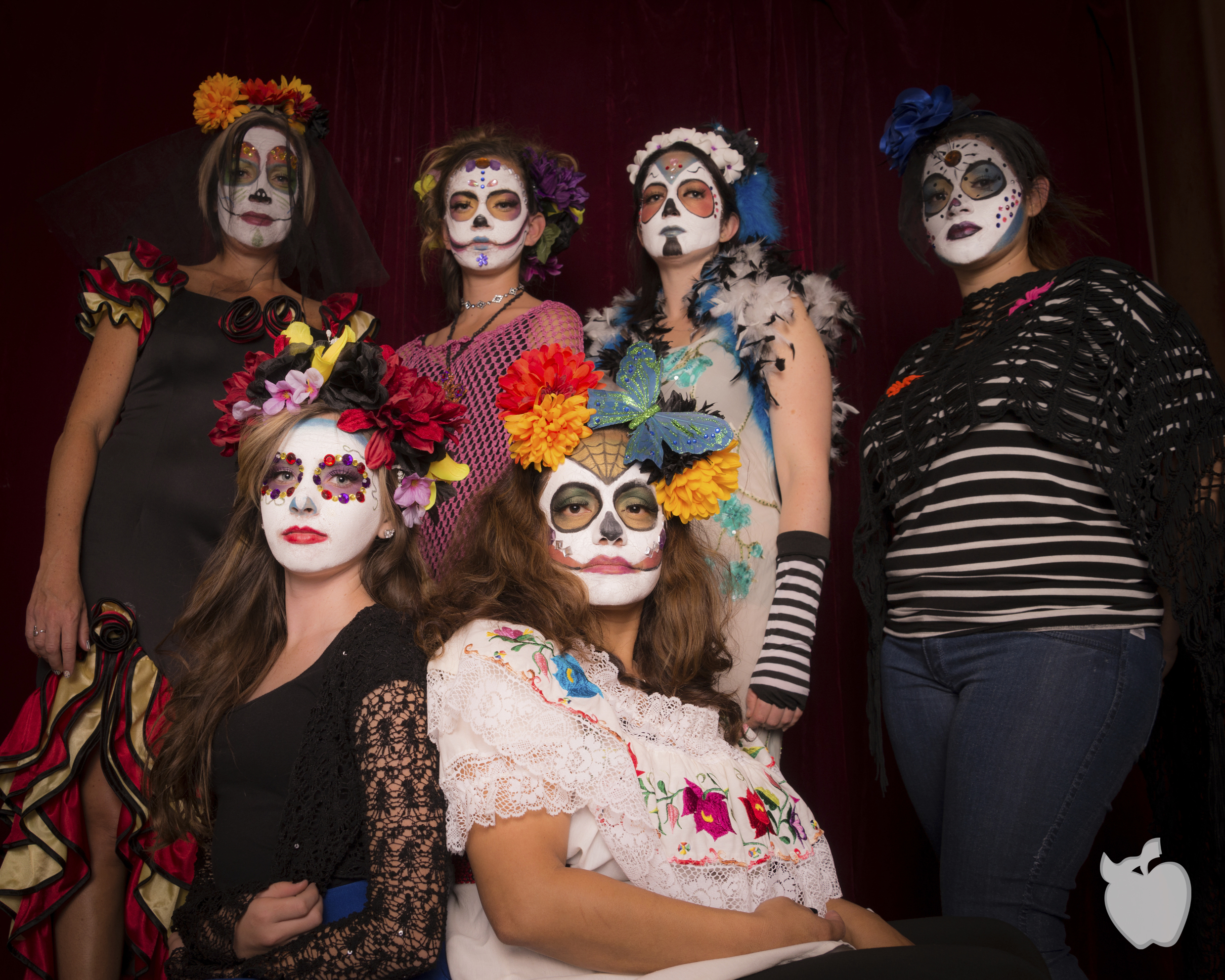 Girls dressed in Day of The Dead costumes and make posing